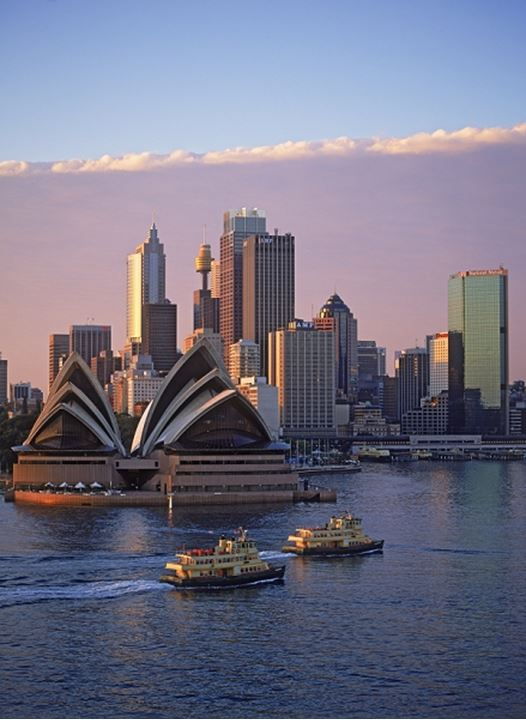 Boat taxis crossing Sydney Harbor with Opera House and skyline at dawn