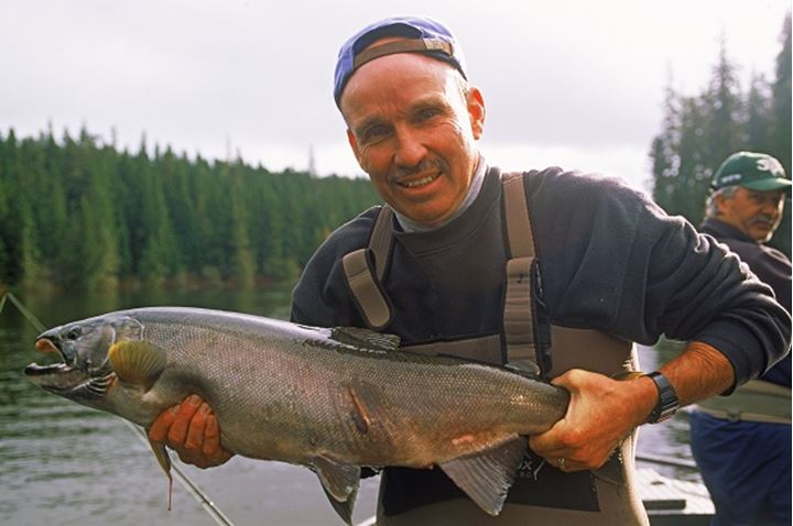 Man holding silver salmon caught in Canadian river