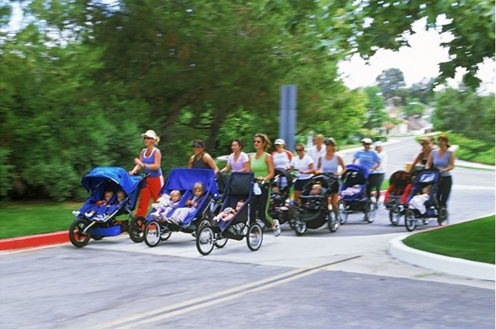 Group of mothers running with baby strollers in California