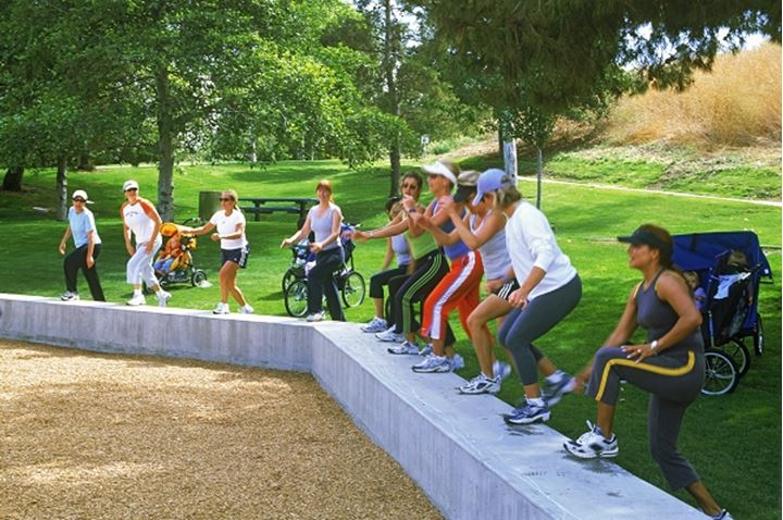 Mothers exercising in California park with baby strollers