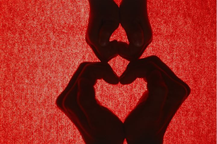 Mother and child forming two hearts with four hands