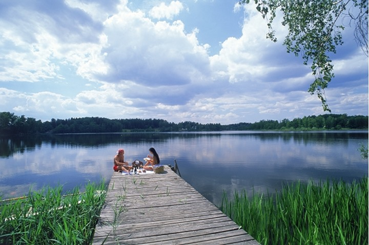 Couple having picnic on lake pier at Yxtaholm in Sweden