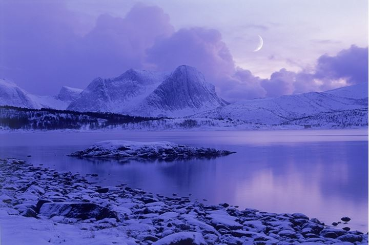 Cresent moon in winter over mountains and Efjord near Skarstad in northern Norway