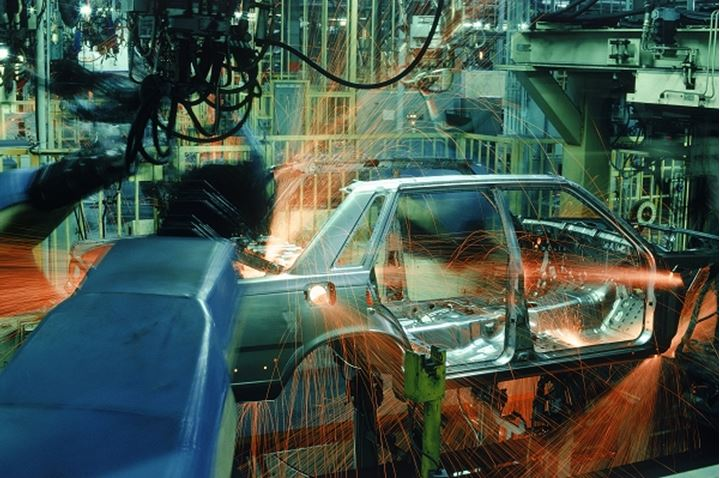 Sparks flying from spot welding robotics at automobile factory