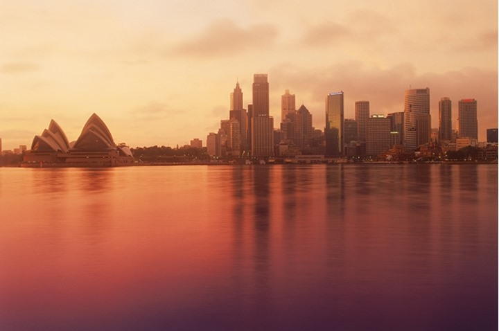 Sydney city skyline with Opera House reflecting off calm harbour waters at sunrise