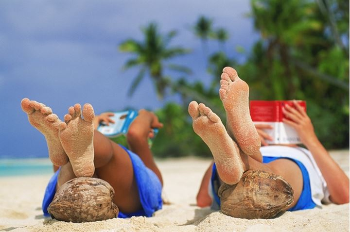 Couple reading books on sandy beach with feet resting on coconuts