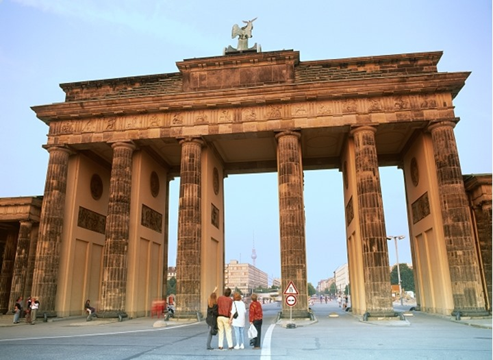 Brandenburg Gate from west side with tourists in sunset light