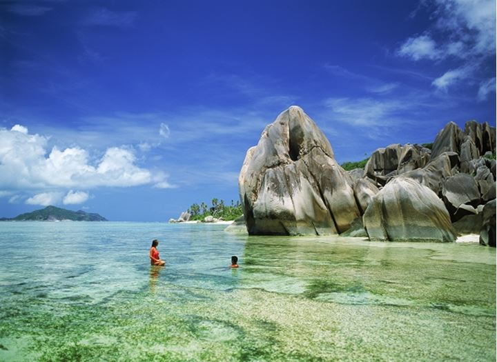 Couple in aqua waters at Anse Source d' Argent on La Digue Island in Seychelles