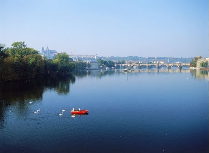 Couple feeding swans from red rowboat on Vltava River with Charles Bridge in Prague