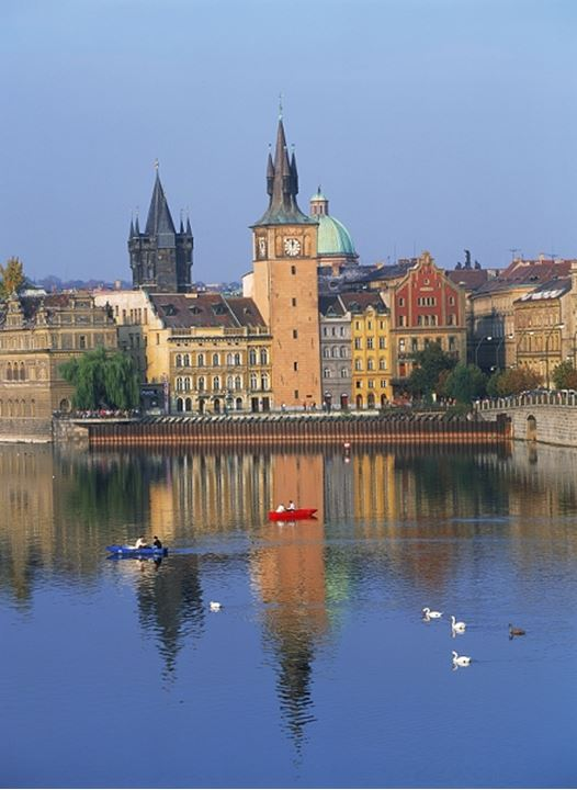 Rowboats and swans on Vltava River in Prague with The Old Town Mills