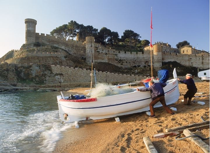 Fishermen and boat on Tossa De Mar beach in Girona Province of Spain at sunrise