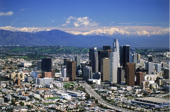 Aerial view of downtown Los Angeles with snow on San Gabriel Mountains