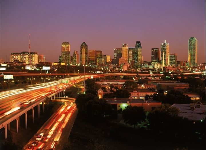 Dallas skyline at sunset with traffic over viaduct