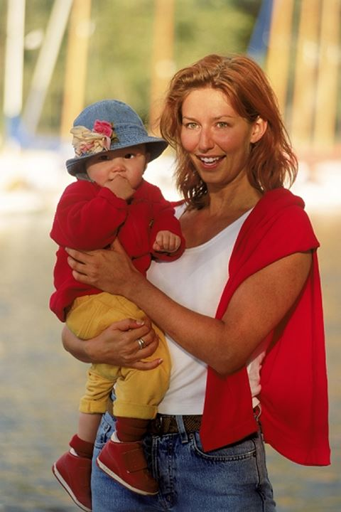 Mother holding daughter dressed in red