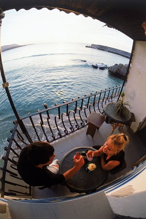 Couple toasting on cafe balcony over water at sunset in Cefalu Sicily