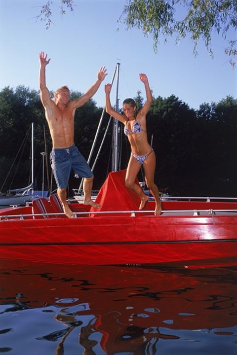 Young couple jumping off red boat into cold water