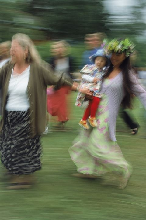 Parents and children dancing around Maypole during Midsummer Celebrations in Sweden