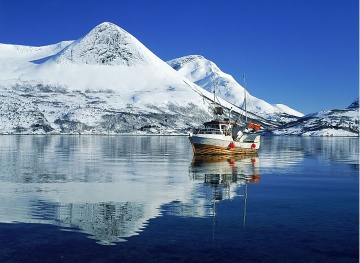 Fishing boat and mountains reflecing off Morsvikbotn Fjord in Northern Norway