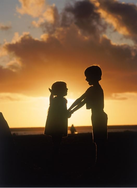 Boy and girl holding eachother at sunset