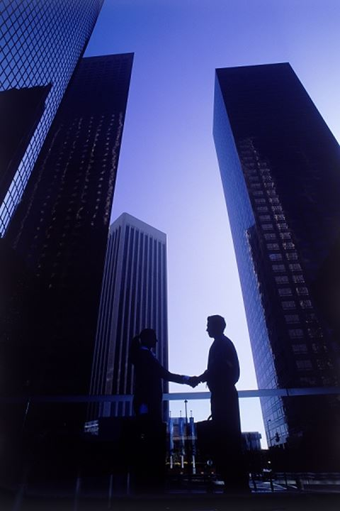 Shaking hands in shadows of skyscrapers in Los Angeles