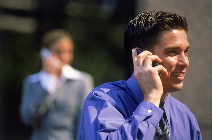 Businessman talking on cellphone with businesswoman behind