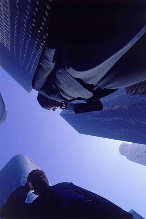 Businesswoman talking on cell phone under Los Angeles skyscrapers