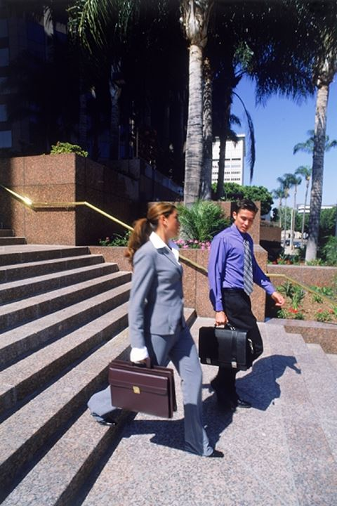 Businessman and women with briefcases on steps in Los Angeles