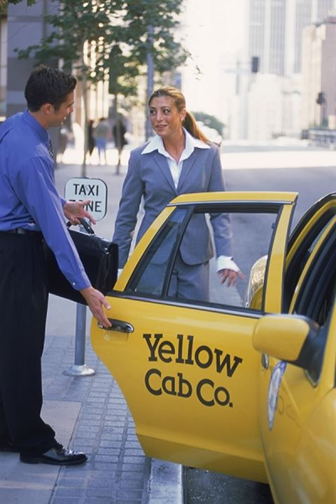 Businessman opening door of taxi for businesswoman in downtown Los Angeles