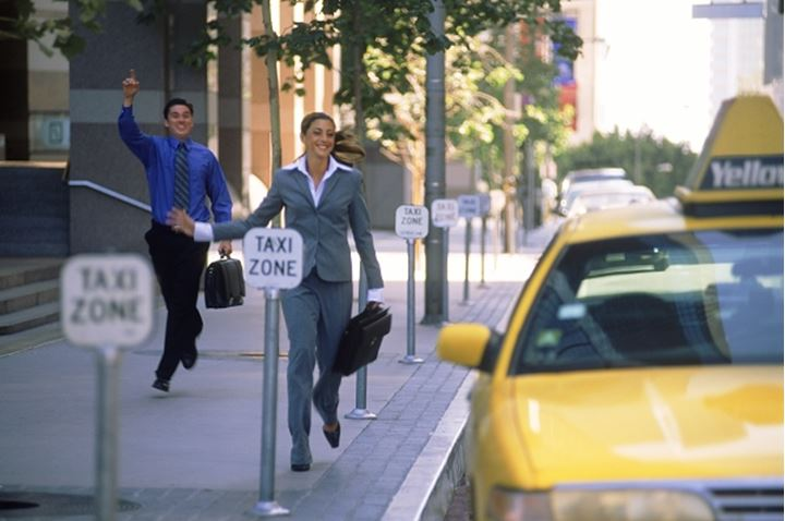 businessman and woman catching taxi in downtown Los Angeles