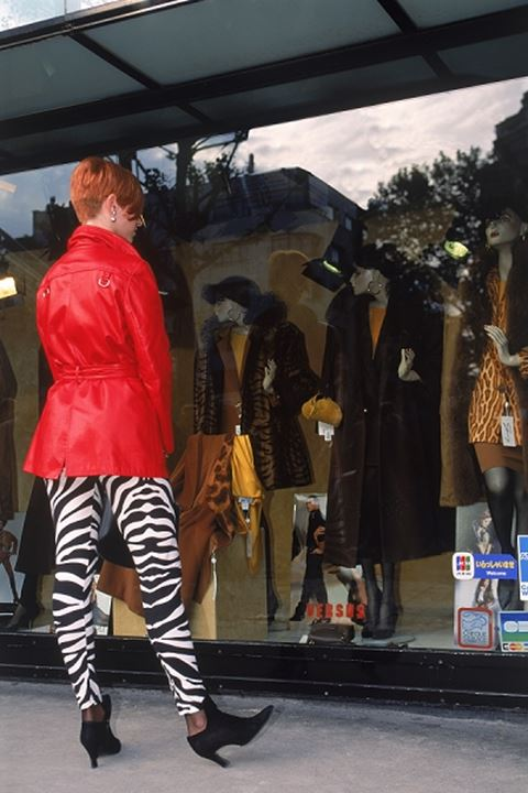 Red head in zebra pants window shopping along Champs Elysees in Paris