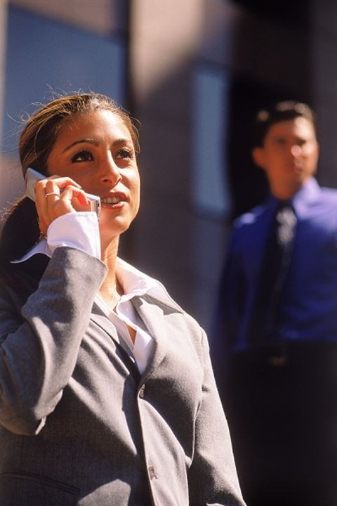Businesswoman talking on cellphone with man behind