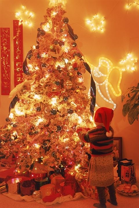 Young girl and brightly lit Christmas tree