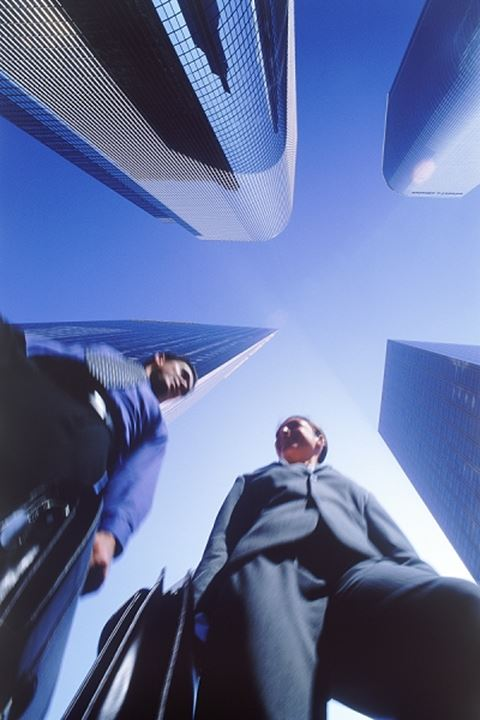 Businessman and women with briefcase walking under Los Angeles skyscrapers