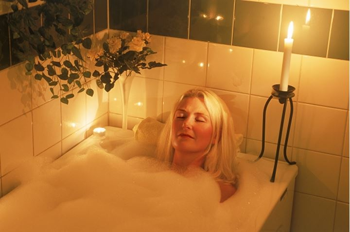 Women soaking in bathtub with bubbles and candles