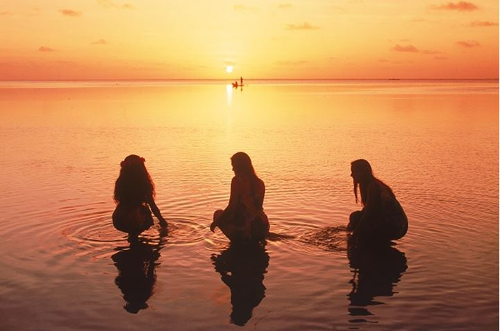 Three young Polynesian woman in Aitutaki Island lagoon at sunset with distant outrigger