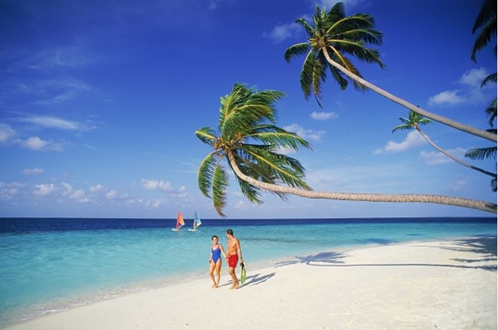 Couple walking on tropical island in Maldives with passing windsailors