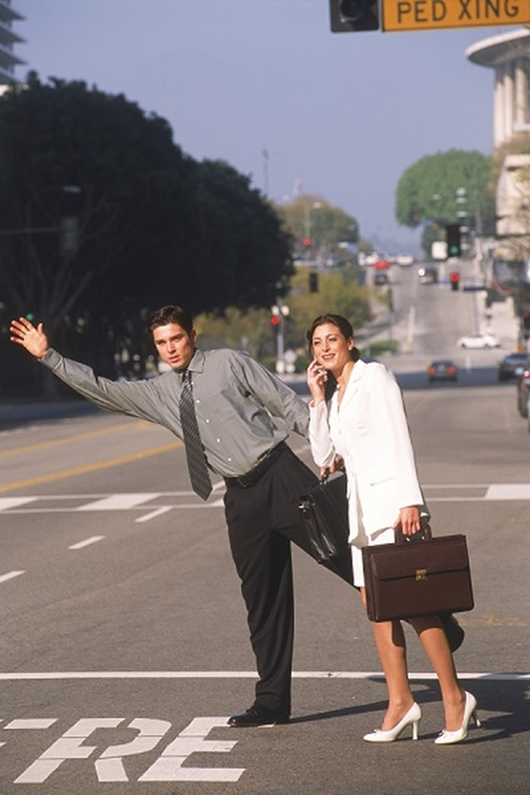 Businessman and woman with briefcases hailing taxi