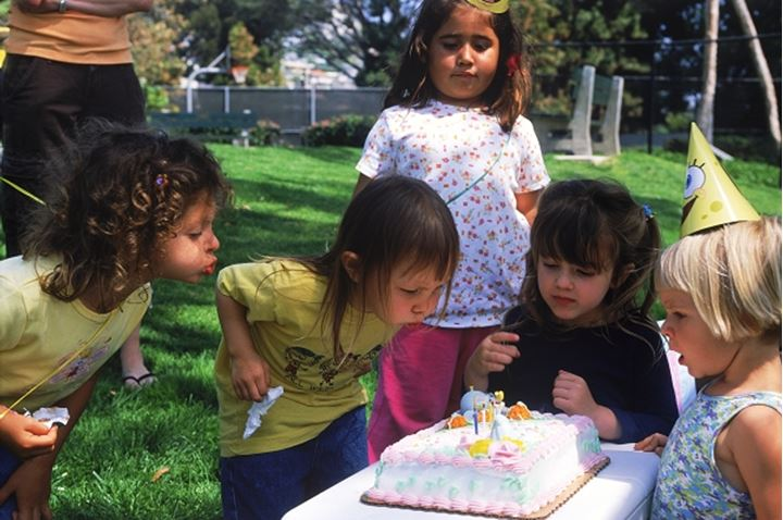 Kids at birthday party blowing out candles