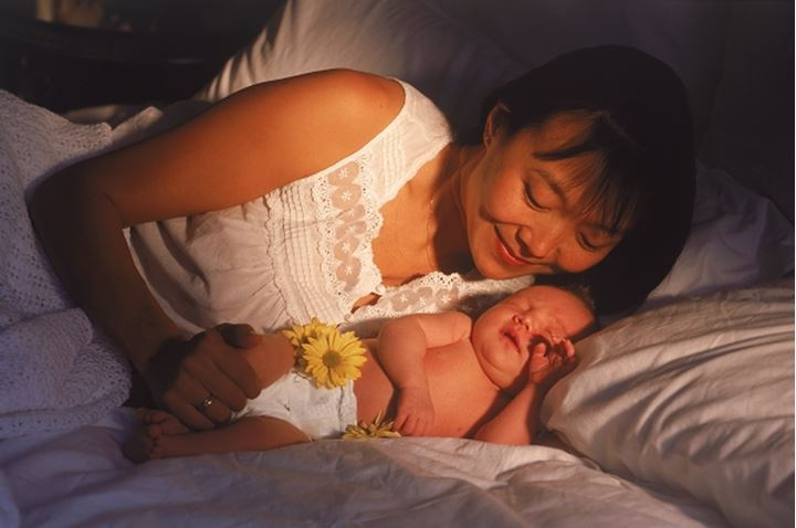 Asian mother with her newborn baby in bedroom morning light