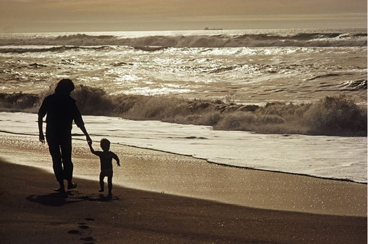 Mother and child silhouetted on wave painted open shore