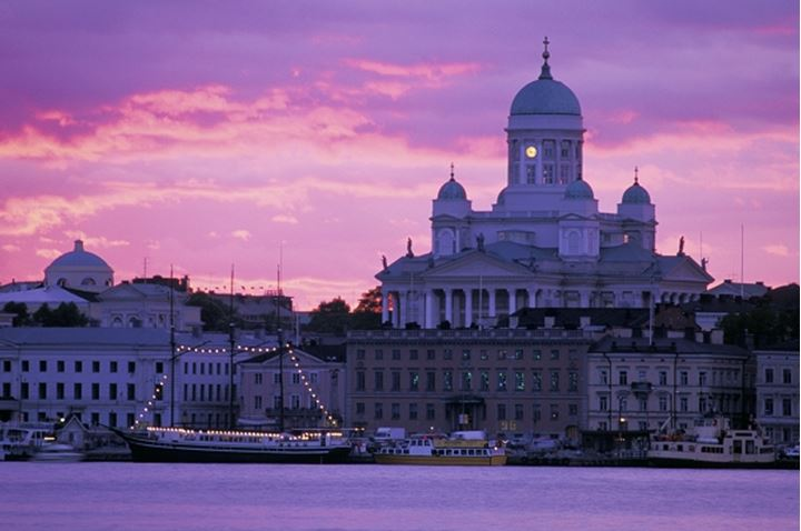 Luthern Cathedral silhouetted over South Harbor with boats moored along waterfront at sunset in Helsinki