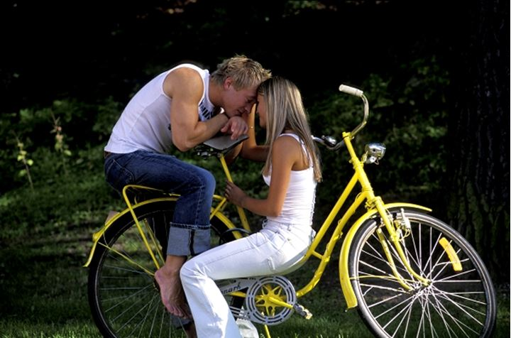 Young couple sitting face to face on yellow bike