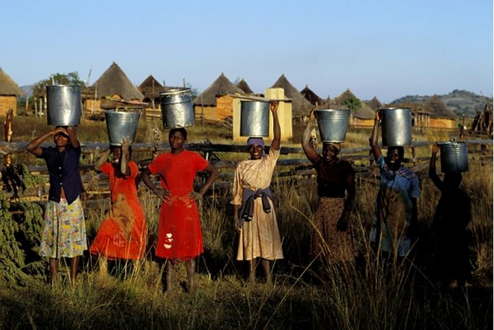 Young women porting buckets of water into rural Zimbabwe village