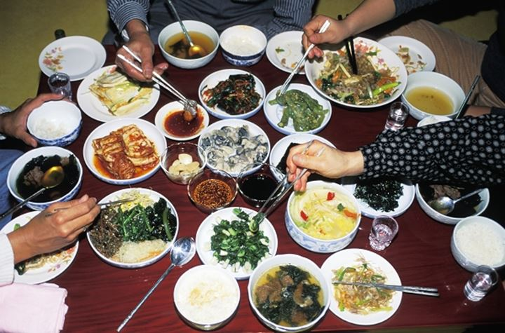 Family eating variety typical Korean food at home