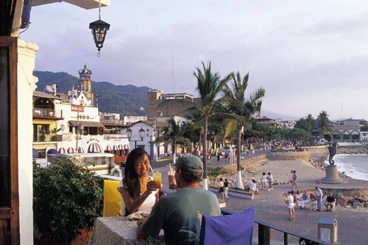Couple having sunset drinks at oceanfront restaurant in Puerto Vallarta Mexico