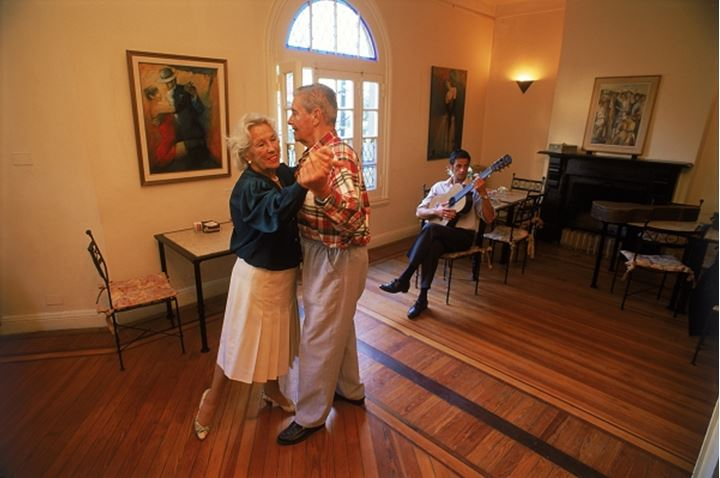 Elderly couple tango dancing to guitar music in Buenos Aires cafe