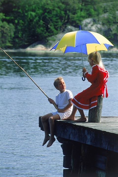 Children fishing off pier under umbrella with Swedish colors