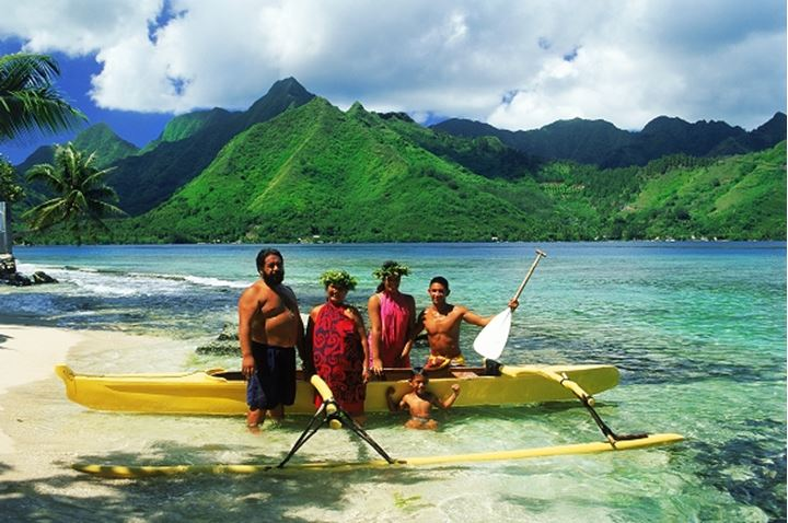 Tahitian family with their outrigger canoe at Opunohu in Moorea