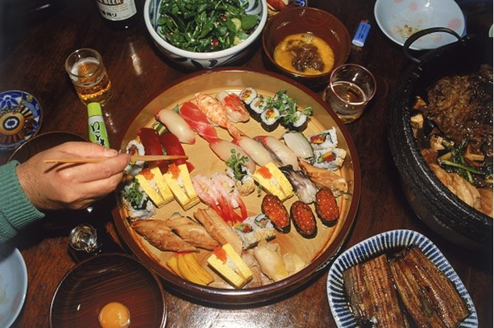 Using chopsticks to eat sushi and variety of Japanese foods