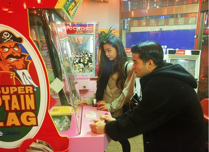 Two teenagers playing action games in Japan